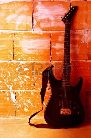 10439350-electric-guitar-on-old-wall-with-copyspace